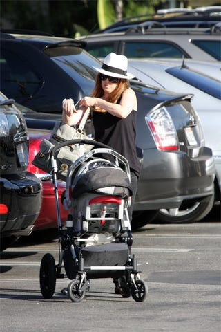 Illustration for article titled Isla Fisher Juggles Baby, Bags
