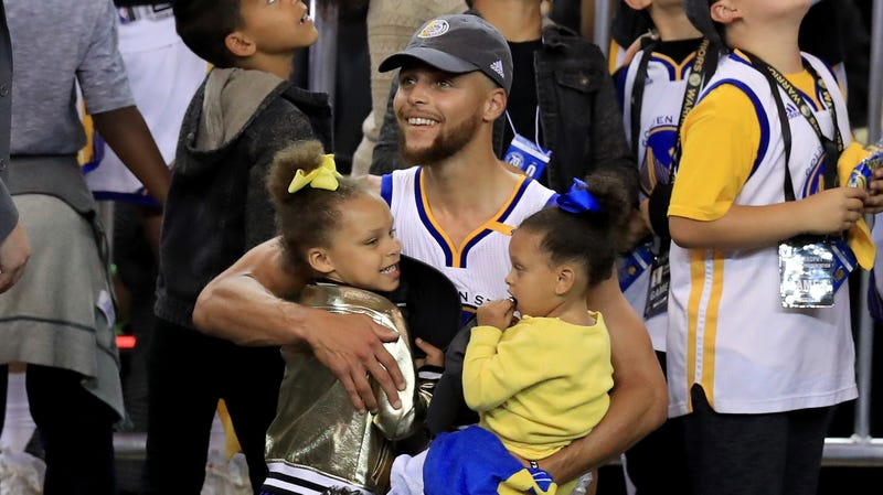 Stephen Curry of the Golden State Warriors celebrates holding daughters Riley and Ryan after defeating the Cleveland Cavaliers 129-120 in Game 5 to win the 2017 NBA Finals on June 12, 2017 in Oakland, California.