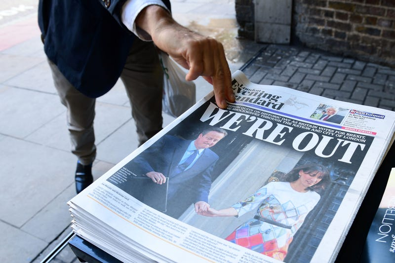 """A man takes a copy of the London Evening Standard with the front page reporting the resignation of British Prime Minister David Cameron and the United Kingdom's vote to leave the European Union with the headline """"We're Out,"""" and a picture of Cameron holding hands with his wife, Samantha, as they come out of 10 Downing Street in London on June 24, 2016.LEON NEAL/AFP/Getty Images"""