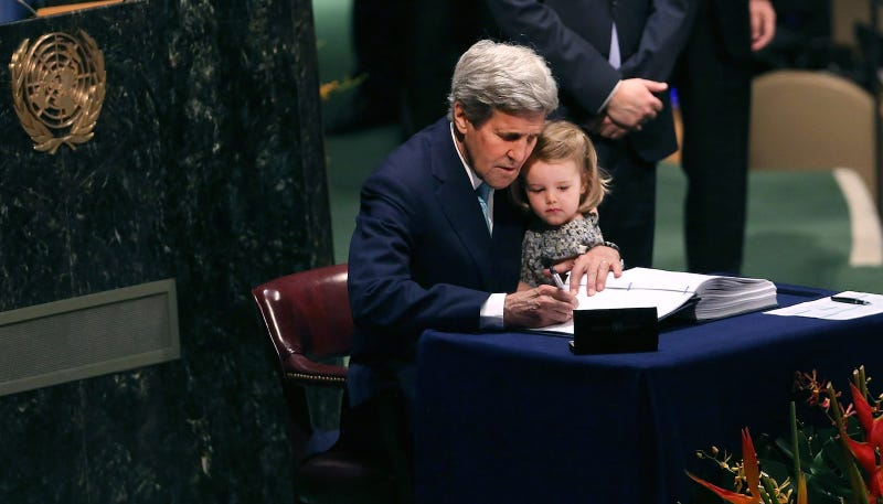 John Kerry and his two-year-old granddaughter sign the Paris Agreement on April 22, 2016. Image via Getty.