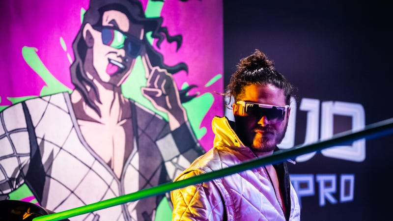 """""""Bad Boy"""" Joey Janela, flanked by his comic book-style banner, prepares for action in the titular dojo."""