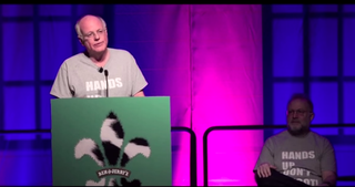 "Ben Cohen, co-founder of Ben & Jerry's, speaks at the company's annual franchisee meeting in January 2015 in New Orleans. Jerry Greenfield, the company's other founder, is in the background. Both are wearing the ""Hands Up Don't Shoot"" T-shirt they're urging fanchisees to sell in their shops.YouTube screenshot"