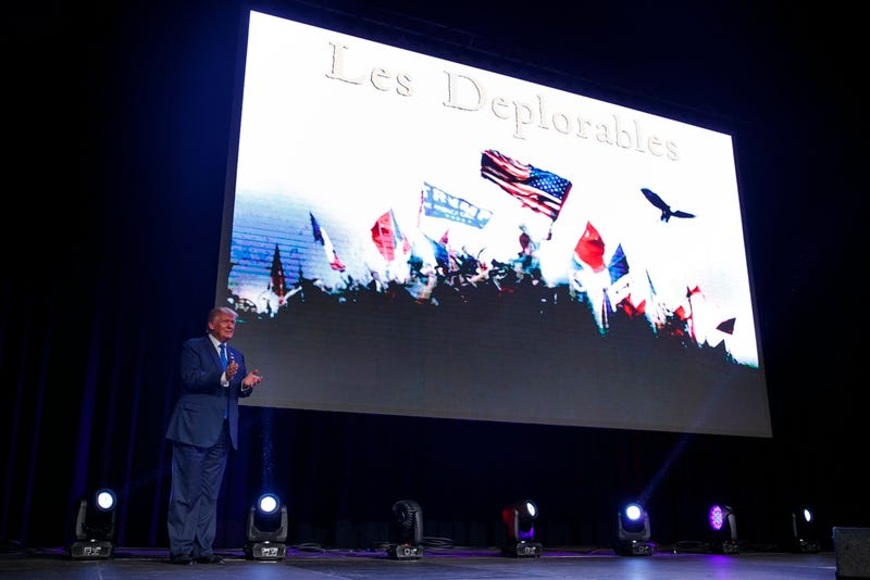 Donald Trump at a rally in Miami in front of a Les Deplorables sign (AP Photo/ Evan Vucci)