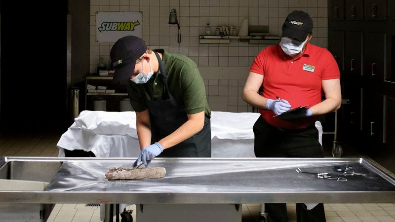A Subway trainee struggles to recognize and classify the various meats present in his Cold Cut Combo cadaver.