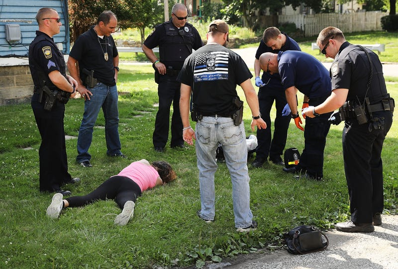 Medical workers and police treat a woman who has overdosed on heroin on July 14, 2017, in Warren, Ohio.