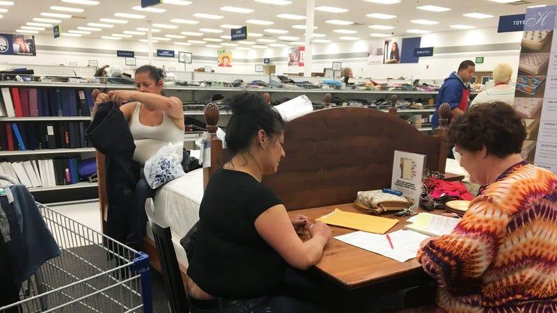A SWOP Sacramento volunteer helping a client with a clothing voucher.