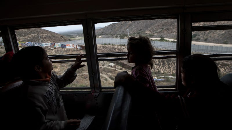Central American children who are traveling with a caravan of migrants, look at the border wall from a bus carrying the group to a gathering of migrants living on both sides of the border, in Tijuana, Mexico, Sunday, April 29, 2018.