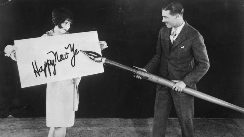 1925: Clara Bow holds up a large card while Larry Gray inscribes a New Year's greeting with a giant pen. (Photo: General Photographic Agency/Getty Images)