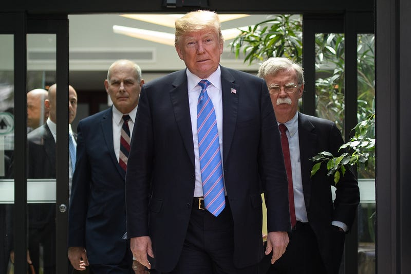 President Donald Trump (C) leaves with Chief of Staff John Kelly (L) and National Security Adviser John Bolton (R) after holding a press conference ahead of his early departure from the G7 Summit on June 9, 2018 in La Malbaie, Canada.