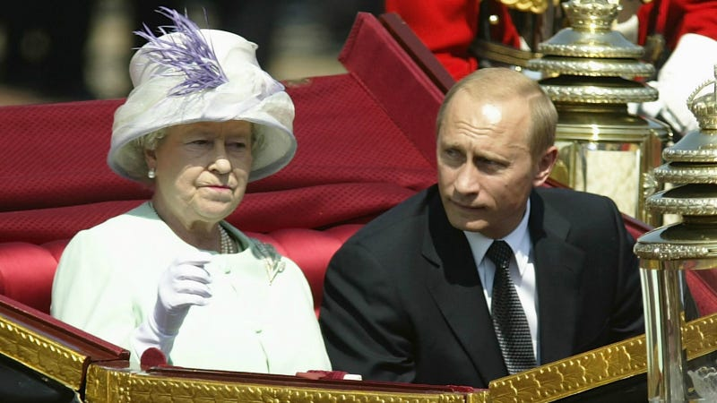 Russian President Vladimir Putin is accompanied by Her Majesty The Queen during a procession at The Mallat during the start iof his state visit on June 24, 2003 in London, England. Photo via Getty Images.