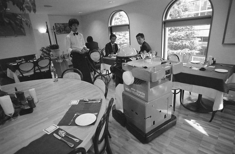 Restaurant manager Mitsugu Watarai operating the Ken-chan robot in Tokyo on November 24, 1985 (Associated Press)