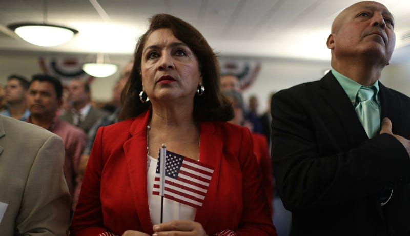 Nelly Siero, originally from Nicaragua, holds an American flag as she becomes an American citizen during a ceremony at the U.S. Citizenship and Immigration Service's Kendall office on November 10, 2016 in Miami, Florida. Photo via Getty