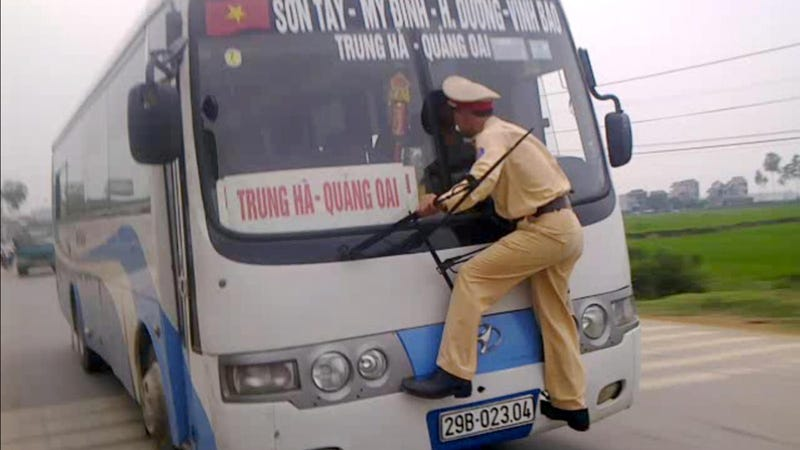 Illustration for article titled Watch A Heroic Vietnamese Cop Cling Desperately To The Windshield Of This Speeding Bus