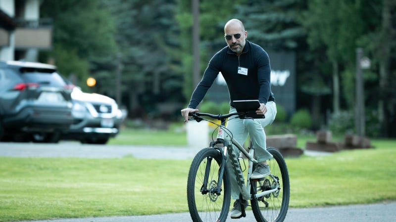Dara Khosrowshahi using some sort of tablet while riding a bike, a photo I will never get sick of looking at