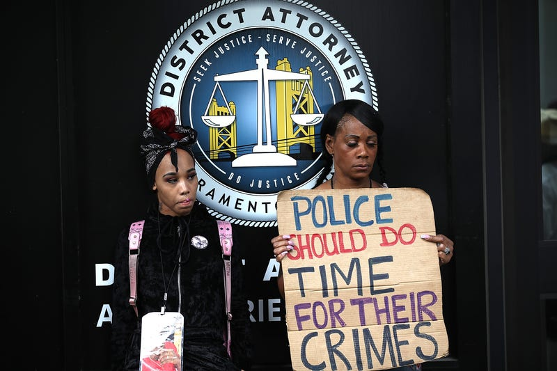 Black Lives Matter protesters hold a sign during a demonstration in front of the offices of Sacramento district attorney Anne Marie Schubert on April 4, 2018 in Sacramento, California.