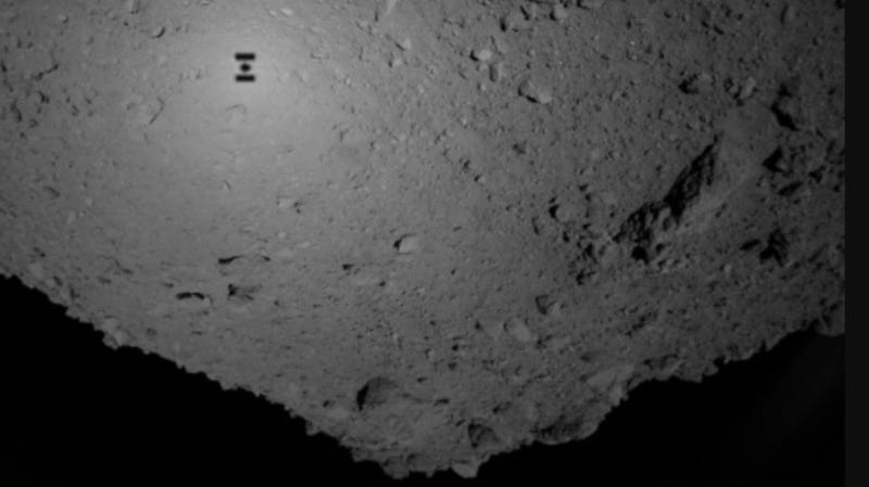 Hayabusa2 flying over the asteroid Ryugu on September 21st, 2018; its shadow can clearly be seen on the object's surface in the upper left corner of the image.