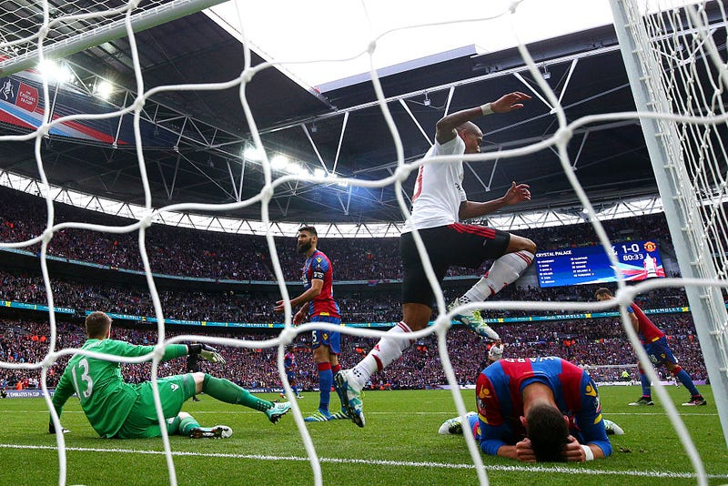 Ashley Young of Manchester United celebrates as goalkeeper Wayne Hennessey (13) and Joel Ward of Crystal Palace (right) look dejected after Man U's first goal. Via Getty Images.