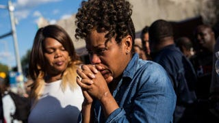 A woman cries after being prayed over during a protest near the CVS pharmacy that was set on fire during rioting after the funeral of Freddie Gray on April 28, 2015, in Baltimore.Andrew Burton/Getty Images