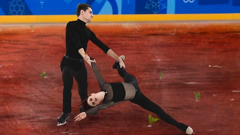 Two figure skaters skating on a rink of frozen V8 juice.