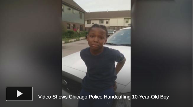 A 10-year-old identified as Michael Thomas Jr. is cuffed by police as an outraged community looks on.