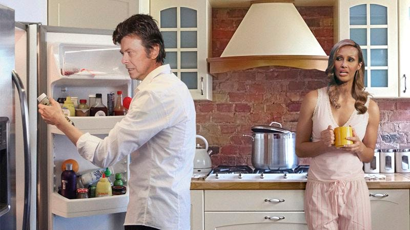 The man who once played the role of a pansexual alien and came to drunken blows with Lou Reed in a restaurant, looks through the fridge with his wife, a Somali supermodel.
