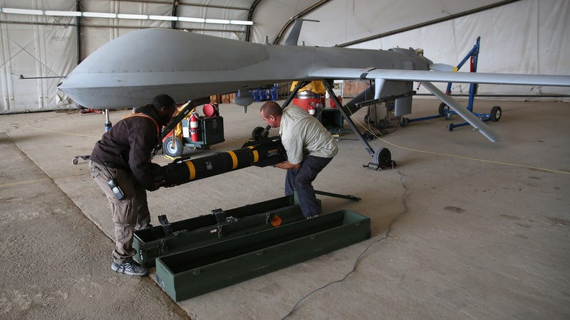 Contract workers load a Hellfire missile onto a U.S. Air Force MQ-1B Predator unmanned aerial vehicle (UAV), at a secret air base in the Persian Gulf region on January 7, 2016.