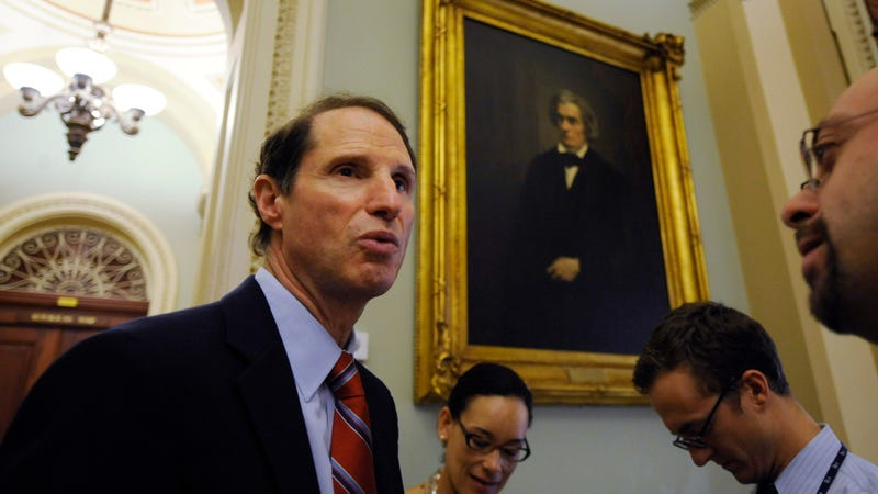 Sen. Ron Wyden, D-Ore., left, talks with reporters on Capitol Hill.