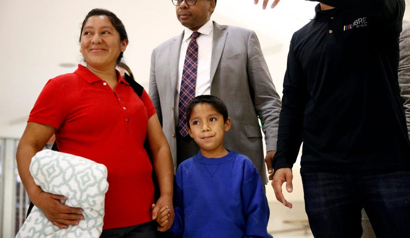 Darwin Micheal Mejia, bottom center, and his mother, Beata Mariana de Jesus Mejia-Mejia, left, are escorted to a news conference following their reunion at Baltimore-Washington International Thurgood Marshall Airport, Friday, June 22, 2018, in Linthicum, Md.