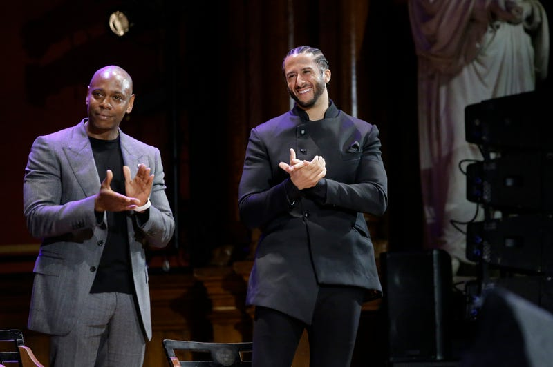 Comedian Dave Chappelle, left, and former NFL quarterback Colin Kaepernick, right, applaud during W.E.B. Du Bois Medal award ceremonies, Thursday, Oct. 11, 2018, at Harvard University, in Cambridge, Mass. Chappelle and Kaepernick are among eight recipients of Harvard University's W.E.B. Du Bois Medals in 2018.
