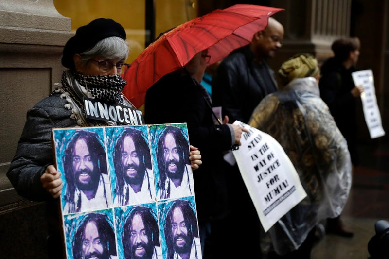 A protester holds up a poster depicting Mumia Abu-Jamal during a demonstration Dec. 28, 2018, outside the offices of Philadelphia District Attorney Larry Krasner.
