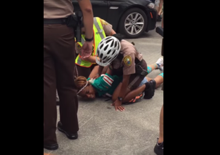 Miko Grimes being pinned to the ground by a Miami-Dade officerYouTube screenshot