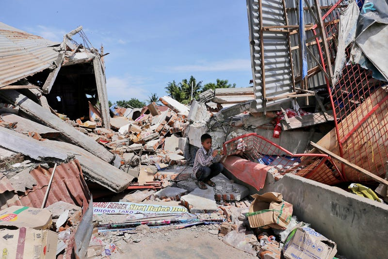 A boy sits on the rubble of a building that collapsed after an earthquake as he takes shelter from the sun in Pidie Jaya. (Image: AP/Heri Juanda)