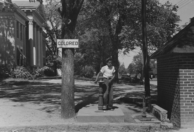 A photograph of an African-American child using a water fountain, which is part of the county courthouse property in Halifax, N.C., in 1938. From the New York Public Library. (Smith Collection/Gado/Getty Images)