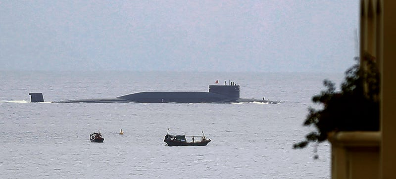 In this Aug. 28, 2014 photo, fishermen look at a Chinese nuclear submarine sails past Yalong Bay in Sanya, south China's Hainan Province. Several Asian nations are arming up, their wary eyes fixed squarely on one country: a resurgent China that's boldly asserting its territorial claims all along the East Asian coast. The scramble to spend more defense dollars comes amid spats with China over contested reefs and waters. Other Asian countries such as India and South Korea are quickly modernizing their forces, although their disputes with China have stayed largely at the diplomatic level. (AP Photo/Andy Wong)