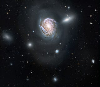 Illustration for article titled A galaxy tears the spiral arms off its neighbor