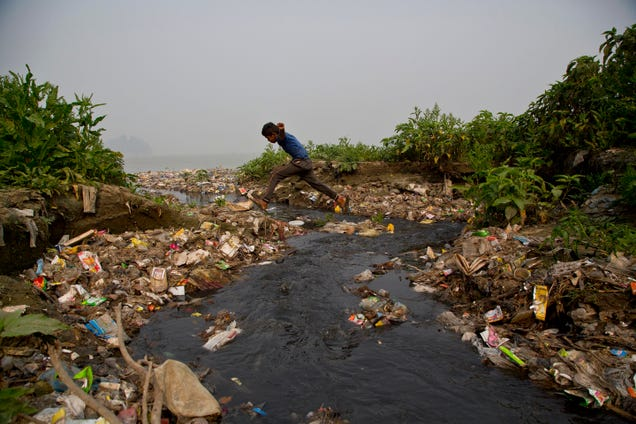 An Indian boy jumps across a polluted water body on World Water Day in Gauhati, India, Thursday, March 22, 2018. According to UNICEF, the U.N.'s children's agency, nearly 78 million Indians, or about 5 percent of the country's 1.3 billion population, must make do with contaminated water sources or buy water at high rates. (AP Photo/Anupam Nath)