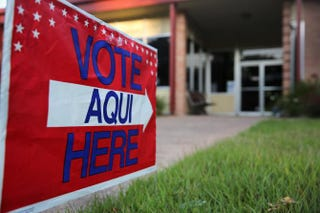 A bilingual sign stands outside a polling center at public library ahead of local elections on April 28, 2013, in Austin, Texas.John Moore/Getty Images