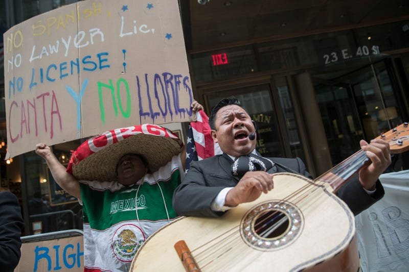 A demonstrator dances and sings along with the Mariachi Tapatio de Alvaro Paulino band as they perform during a demonstration across the street from the building that once housed the office space of Aaron Schlossberg on May 18, 2018, in New York City,