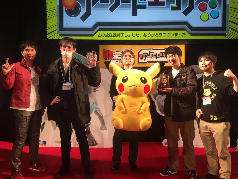 Pokken's producer holding a giant stuffed Pikachu beside the Tokaigi tournament winners.