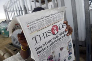 A man reads a newspaper with a headline on July 27, 2014, announcing government efforts in Lagos, Nigeria, to screen for Ebola. PIUS UTOMI EKPEI/AFP/Getty Images