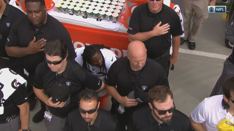 Coaches and staff of the Oakland Raiders gather around running back Marshawn Lynch in an attempt to obscure him as he sits during the national anthem during a game. (@SBNation via Twitter)