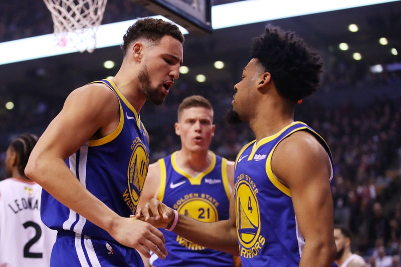 Klay Thompson, left, and Quinn Cook, right, of the Golden State Warriors celebrate the play against the Toronto Raptors.