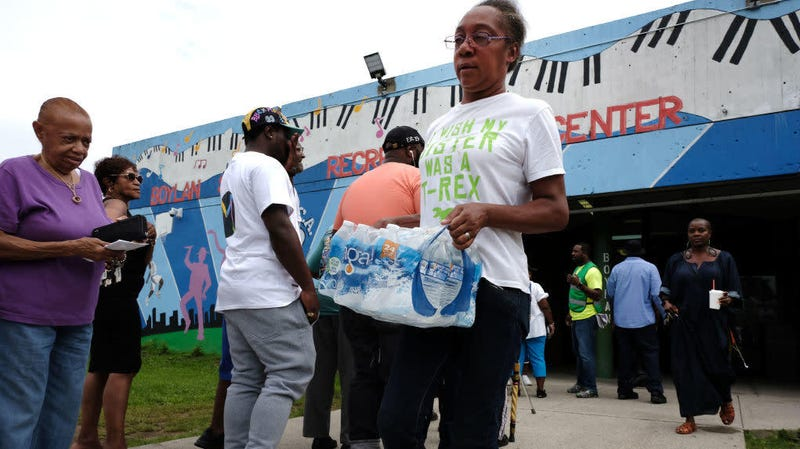 A woman leaves a recreation center after receiving free bottled water on Aug. 13, 2019, in Newark, N.J.