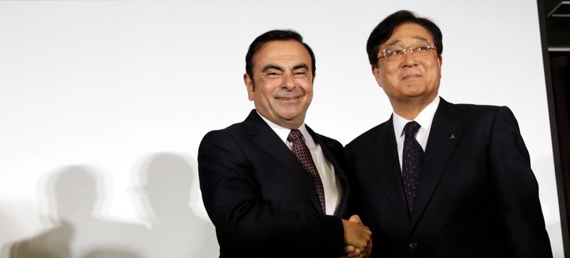 Nissan Motor Co. President and CEO Carlos Ghosn, left, and Mitsubishi Motors Corp. Chairman and CEO Osamu Masuko pose for photographers after their joint press conference at the Nissan headquarters in Yokohama, near Tokyo, Thursday, May 12, 2016. Photo credit AP