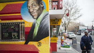 A man walks past a mural of comedian Bill Cosby painted on the side of Ben's Chili Bowl in Washington, D.C., on Dec. 4, 2014.JIM WATSON/AFP/Getty Images