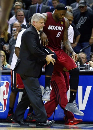LeBron James of the Miami Heat is helped off the court after cramping up against the San Antonio Spurs during Game 1 of the 2014 NBA Finals at the AT&T Center June 5, 2014, in San Antonio. Andy Lyons/Getty Images