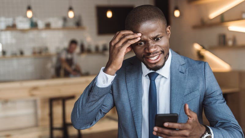 Angry African American businessman gesturing and using smartphone in cafe
