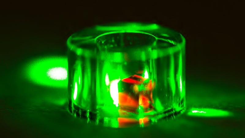 A diamond inside a sapphire ring lit by a green laser.