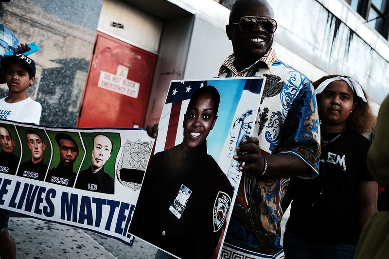"""Calvin Hunt stands with his son Cameron while holding a Blue Lives Matter banner and a picture of New York City Police Officer Miosotis Familia outside a Bronx, N.Y., church during the funeral July 11, 2017, for Officer Familia, who was shot and killed last week in what police have called """"an unprovoked attack"""" as she sat in an NYPD mobile command vehicle. (Spencer Platt/Getty Images)"""