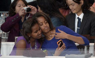 Sasha and Malia Obama take a photo of themselves during the presidential inaugural parade Jan. 21, 2013, in Washington, D.C. JOE KLAMAR/AFP/Getty Images